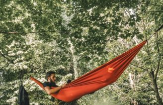 Man in hammock reads adventure book